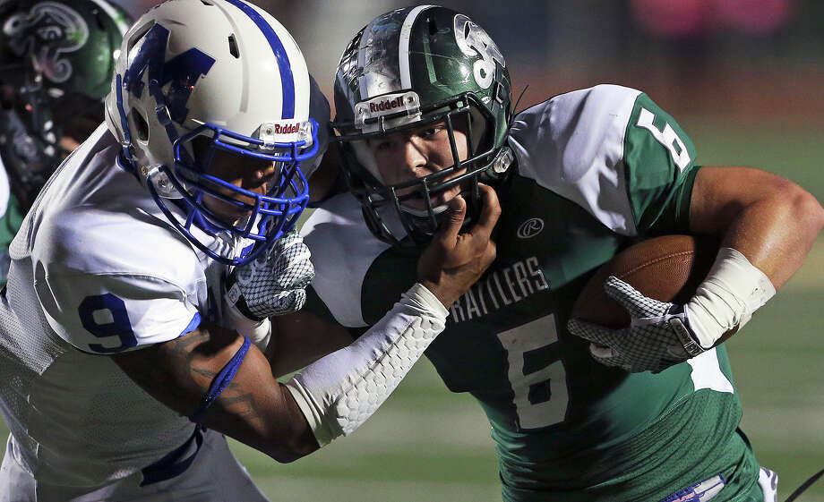 Rattler running back Skyler Wetzel fights to stay up against Dwight Riley in the first quarter as MacArthur plays Reagan at Comalander Stadium on October 24, 2014. No penalty was called on the play. Photo: TOM REEL, By Tom Reel/Express-News