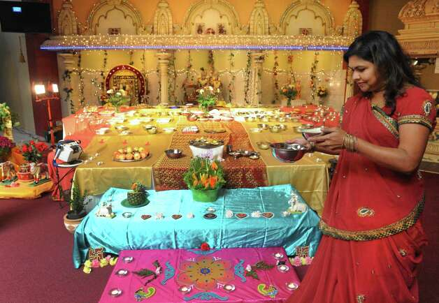 Ratna Randive of Niskayuna, right, sets up the Annakut table with over 50 different food dishes as the local Hindu community celebrates Diwali at the Albany Hindu Temple on Saturday Oct. 25, 2014 in Loudonville, N.Y. (Michael P. Farrell/Times Union) Photo: Michael P. Farrell / 00029185A