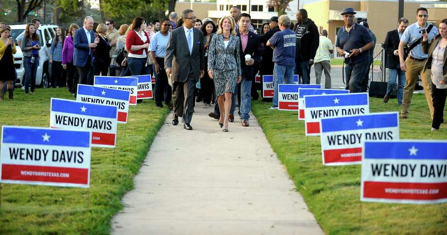 Texas gubernatorial Democratic candidate Wendy Davis, center, walks to a poll in Fort Worth to cast her ballot on the first day of early voting. Photo: Max Faulkner, MBI / The Fort Worth Star-Telegram