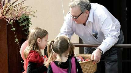 Roberto Moro, the manager of La Zingara Ristorante, in Bethel, hands out treats in front of the restaurant for the Bethel Chamber of Commerce annual Trick or Treat Street Halloween Bash in downtown Bethel, Conn, on Saturday, October 25, 2014. Sisters Grace Guasco, 6, left, and Mackenzie Guasco, 7, of Danbury, try and decide which to pick.