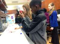 Tayvon Ward, 13, of Shaker Junior High, inspects a solution of extracted strawberry DNA at a student activity in the RNA Institute at the University at Albany on Oct. 25, 2014. (Brittany Horn/Times Union)