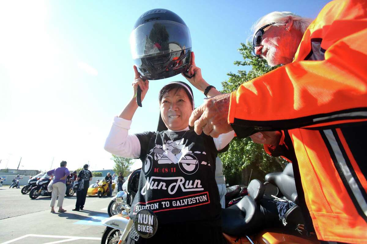 Sister Kim Tran puts on a helmet as riders get ready to rollout in the 10th Annual Nun Run that benefits the Christus Foundation on Saturday, Oct. 25, 2014, in Houston.