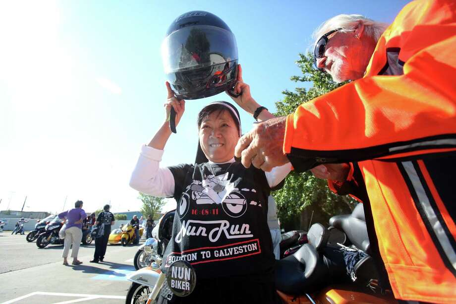 Sister Kim Tran puts on a helmet as riders get ready to  rollout in the 10th Annual Nun Run that benefits the Christus Foundation on Saturday, Oct. 25, 2014, in Houston. Photo: Mayra Beltran, Houston Chronicle / © 2014 Houston Chronicle