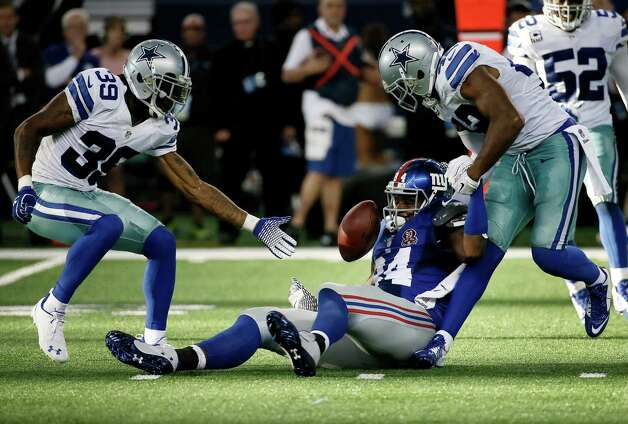 Dallas Cowboys cornerback Brandon Carr (39) watches as free safety Barry Church (42) causes New York Giants tight end Larry Donnell (84) to fumble during the second half of an NFL football game, Sunday, Oct.  19, 2014, in Arlington, Texas. cornerback Brandon Carr (39) reaches for the ball. (AP Photo/Brandon Wade)  ORG XMIT: CBS193 Photo: Brandon Wade / FR168019 AP