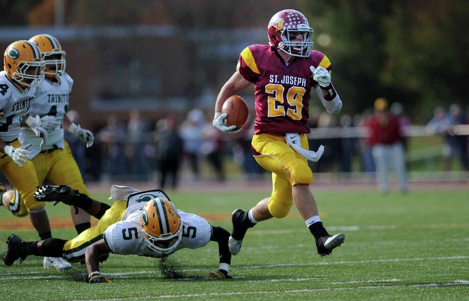 St. Joseph's Lars Pedersen shakes off an attempted tackle by Trinity's Randy Polonia on his way to a touchdown during their game Saturday, Oct. 25, 2014 at St. Joseph High in Trumbull, Conn. Photo: Autumn Driscoll / Connecticut Post