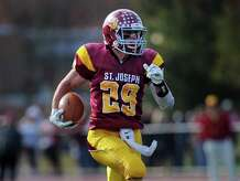 St. Joseph's Lars Pedersen shakes off an attempted tackle by Trinity's Randy Polonia on his way to a touchdown during their game Saturday, Oct. 25, 2014 at St. Joseph High in Trumbull, Conn.