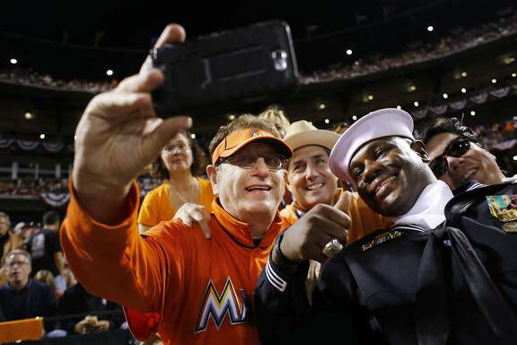 """Laurence """"Marlins Man"""" Leavy poses for a selfie with Dave Martin and Steven Powell behind home plate during game three of the World Series at AT&T park on Friday Oct. 24, 2014 in San Francisco, Calif."""