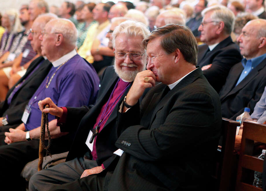 Robert Hibbs (left), a retired bishop suffragan,looks over at the Rt. Rev. David Reed Saturday Oct. 25, 2014 as Reed returned to his seat after giving a short speech when it was announced he was elected coadjutor bishop of the Episcopal Diocese of West Texas. About 400 delegates from the diocese voted during the special council to elect a bishop coadjutor at TMI-The Episcopal School of Texas. Reed who is currently the Bishop Suffragan of the Diocese, was one out of six nominees for the position and won on the first ballot taken, which has only happened one other time, in 1943. Reed will take over in 2017 when the current bishop, the Rt. Rev. Gary Lillibridge will retire. Photo: Cynthia Esparza, For The San Antonio Express-News / For the San Antonio Express-News