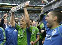 Seattle Sounders midfielder Osvaldo Alonso, center. holds up the Supporters' Shield trophy as Sounders' Clint Dempsey looks on at right after the Sounders beat the Los Angeles Galaxy 2-0 in an MLS soccer match, Saturday, Oct. 25, 2014, in Seattle. The Supporters' Shield is awarded to the MLS team with the best regular-season record. (AP Photo/Ted S. Warren)