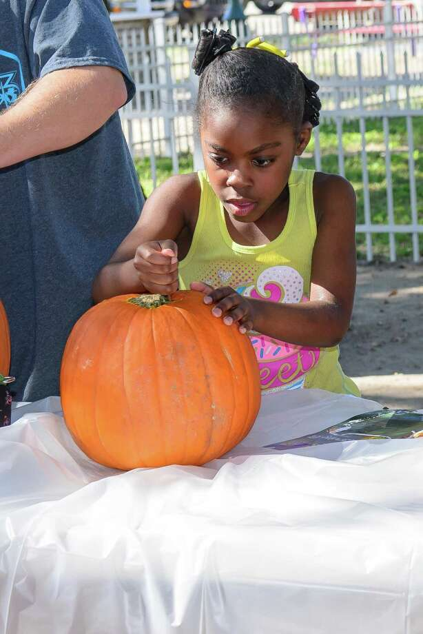 Leslie Bolivar, 8 of Webster concentrates on carving her pumpkin while participating in the pumpkin carving contest during the 20th Annual League City Harvest Festival  this weekend League Park, League City.  10/25/14 Photo: ÂKim Christensen, Photographer / ©Kim Christensen