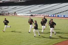 Giants pitchers, including Tim Lincecum, center, warm up in the outfield during batting practice at AT&T Park before Game 4 of the World Series on October 25, 2014 in San Francisco, Calif.