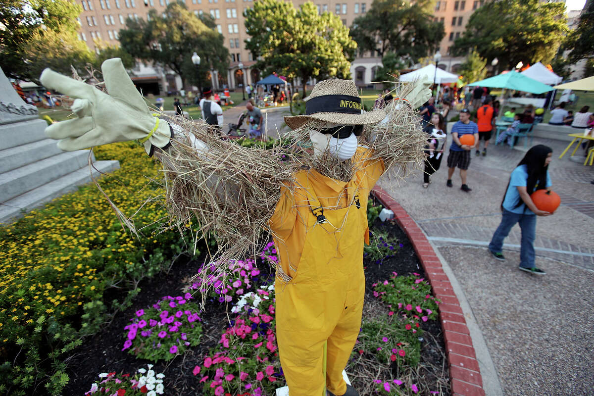 People pass a scarecrow that was part of the scarecrow competition, during the Fall Festival held Saturday, Oct. 25, 2014, in Travis Park in San Antonio. Every year, Comfort, Texas asks residents to create scarecrows for a competition.