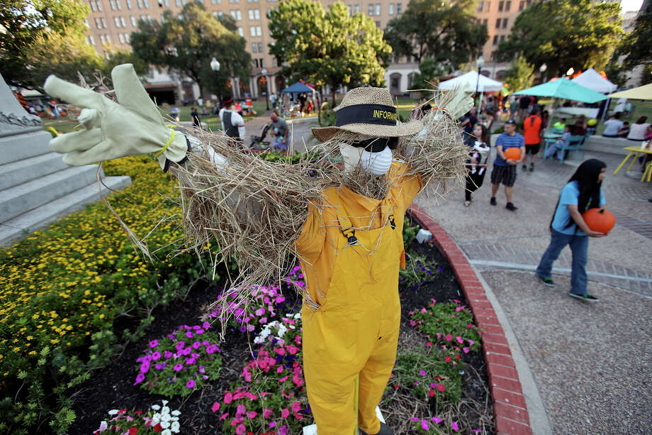 People pass a scarecrow that was part of the scarecrow competition, during the Fall Festival held Saturday, Oct. 25, 2014, in Travis Park in San Antonio. Every year, Comfort, Texas asks residents to create scarecrows for a competition. Photo: Edward A. Ornelas, San Antonio Express-News / © 2014 San Antonio Express-News