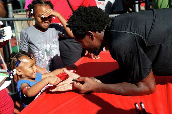 The sun, or budding Rockets star Pat Beverley, can be bright as he greets Kennedi Person, 3, during the autograph session at the Fan Fest at Toyota Center.