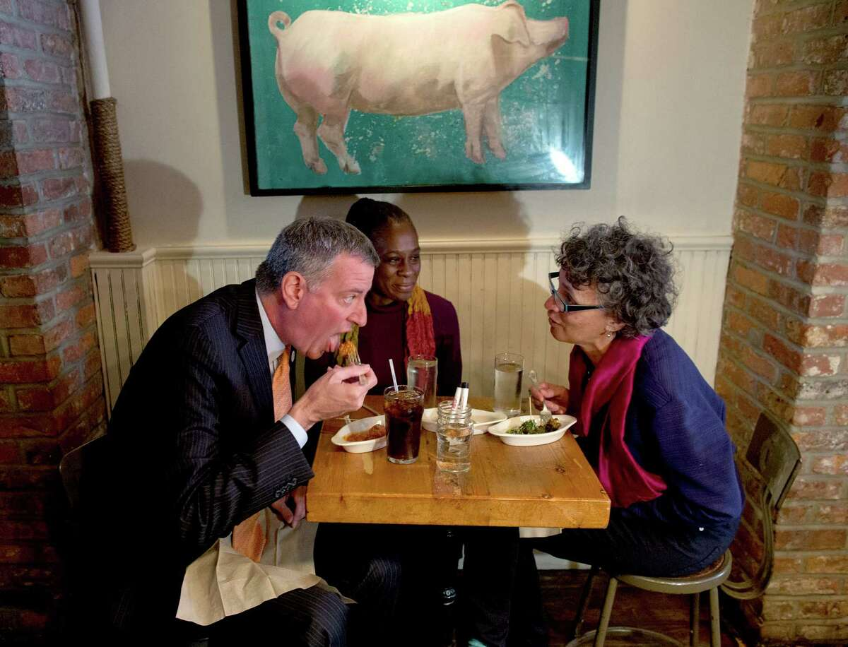 From left, New York City Mayor Bill de Blasio, wife Chirlane McCray, and then-New York City Health Commissioner Dr. Mary Bassett have a meal at The Meatball Shop in New York, Saturday, Oct. 25, 2014, where Dr. Craig Spencer, an Ebola patient, ate just before he became ill. Spencer remained in stable condition while isolated in a hospital, talking by cellphone to his family and assisting disease detectives who are accounting for his every movement since arriving in New York from Guinea via Europe on Oct. 17. (AP Photo/Craig Ruttle)