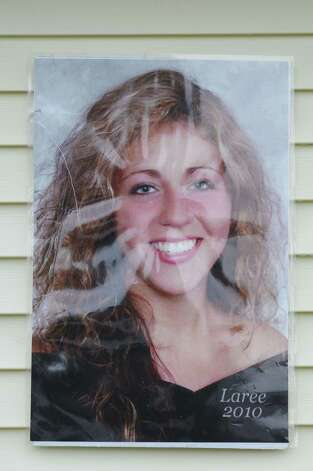 A photo of Laree Farrell hang on a neighbors building next to Patty Farrell's backyard Thursday  May 22, 2014, in Colonie, N.Y. Laree died of a heroin overdose at her mother's home March 16, 2013. (Will Waldron/Times Union) Photo: WW / 00027007A