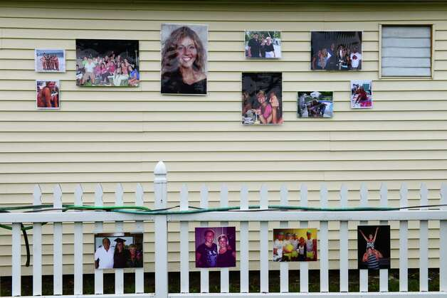 Photos of Laree Farrell hang on a neighbors building next to Patty Farrell's backyard Thursday,  May 22, 2014, in Colonie, N.Y. Laree died of a heroin overdose at her mother's home  March 16, 2013. (Will Waldron/Times Union) Photo: WW / 00027007A