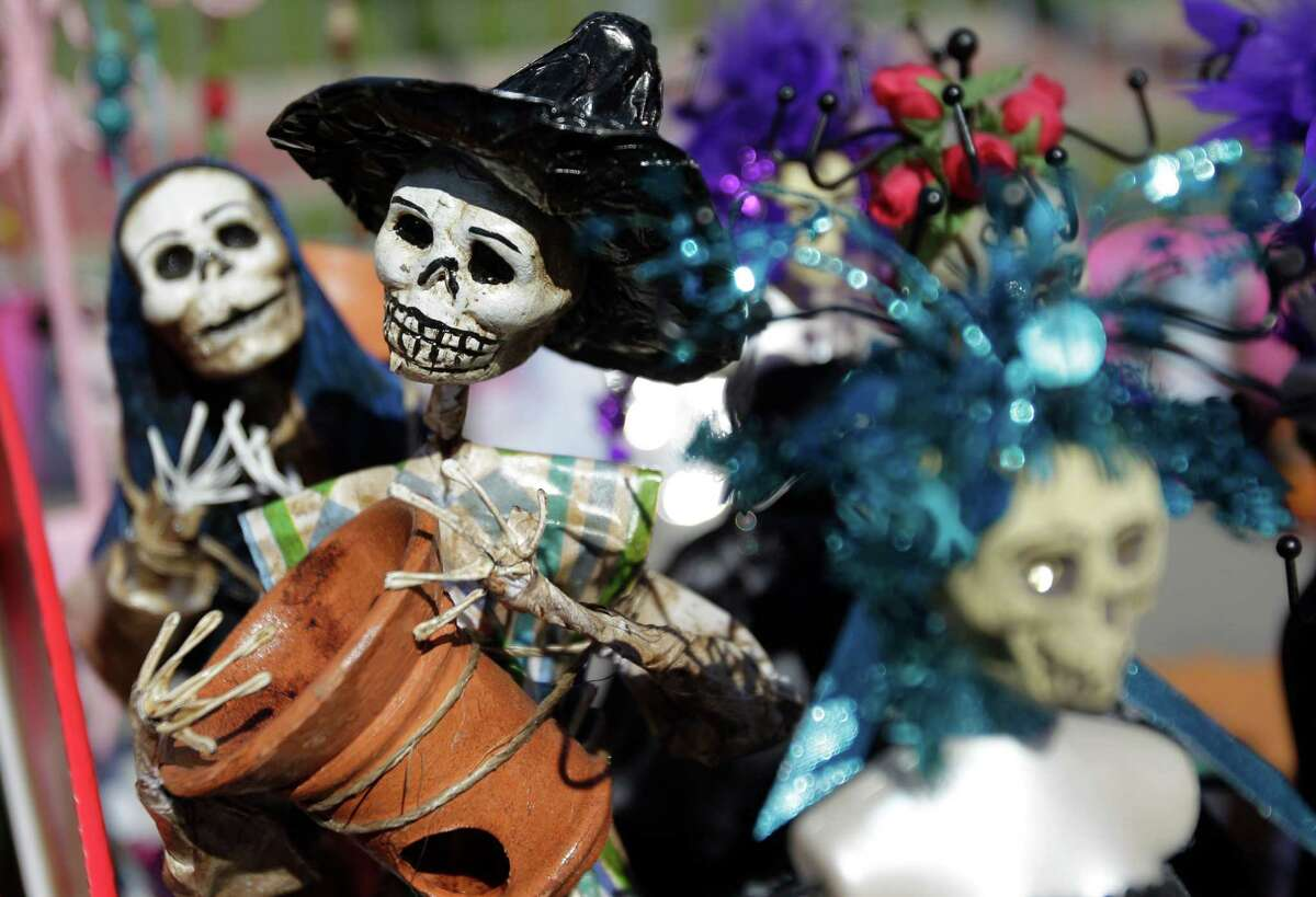 Day of the Dead figurines on display at The East End Street Festival on Saturday, Oct. 25, 2014, in Houston.