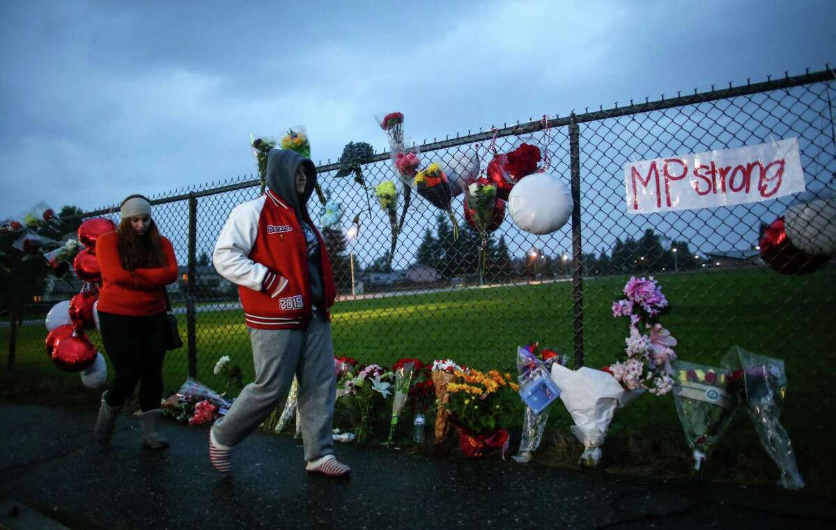 A memorial grows at the entrance to Marysville Pilchuck High School the day after a shooting in the school cafeteria left two dead and four wounded. The shooter was among the dead. A first year teacher was being hailed as a hero for intervening in the shooting, possibly stopping the gunman. Photographed on October 25, 2014.