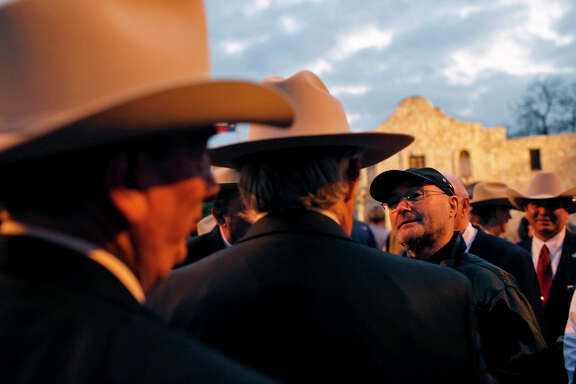 Singer and Alamo collector Phil Collins, shown here at a 2009 appearance at the state shrine with members of the Sons of the Republic of Texas, will return his collection of artifacts to San Antonio this week.
