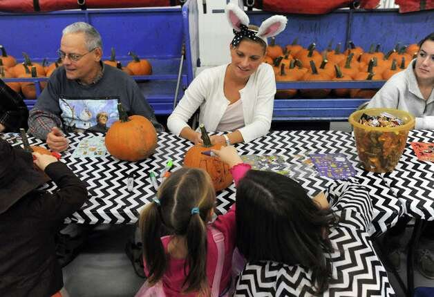 Southwest employee Stephanie Macherone, center in rabbit ears, helps with pumpkin decorating during the Southwest Airlines hosted annual Halloween party for wish kids from Make-A-Wish Northeast New York in the Hildt Aviation Hangar at Albany International Airport on Saturday Oct. 25, 2014 in Colonie, N.Y. (Michael P. Farrell/Times Union) Photo: Michael P. Farrell / 00029167A