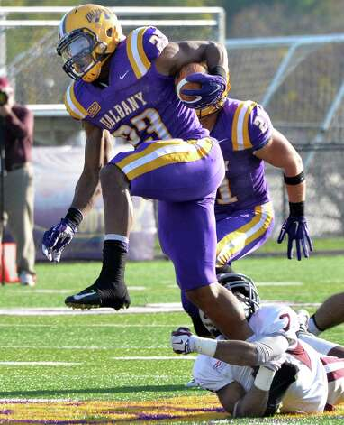 UAlbany's # 23 Omar Osbourne, left, leaps out of the grip of Colgate's #7 Keyon Washington during Saturday's game at Bob Ford Field  Oct. 25, 2014, in Albany, NY.  (John Carl D'Annibale / Times Union) Photo: John Carl D'Annibale / 00029094A