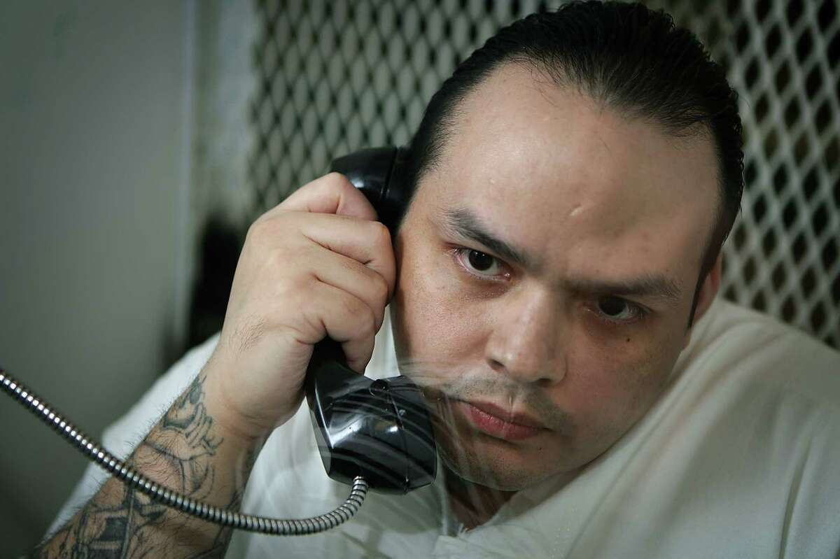Miguel Angel Paredes, 32, is interviewed behind a heavy glass window on death row at the state prison in Livingston.