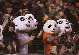 Fans wearing panda heads cheer in the fifth inning during Game 4 of the World Series at AT&T Park on Saturday, Oct. 25, 2014 in San Francisco, Calif.