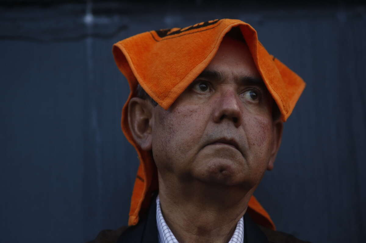 Giants fan Hector Valderama, of Monterey, Mexico, uses a rally rag to ward off rain during game four of the World Series at AT&T park against the Kansas City Royals on Friday Oct. 25, 2014 in San Francisco, Calif.