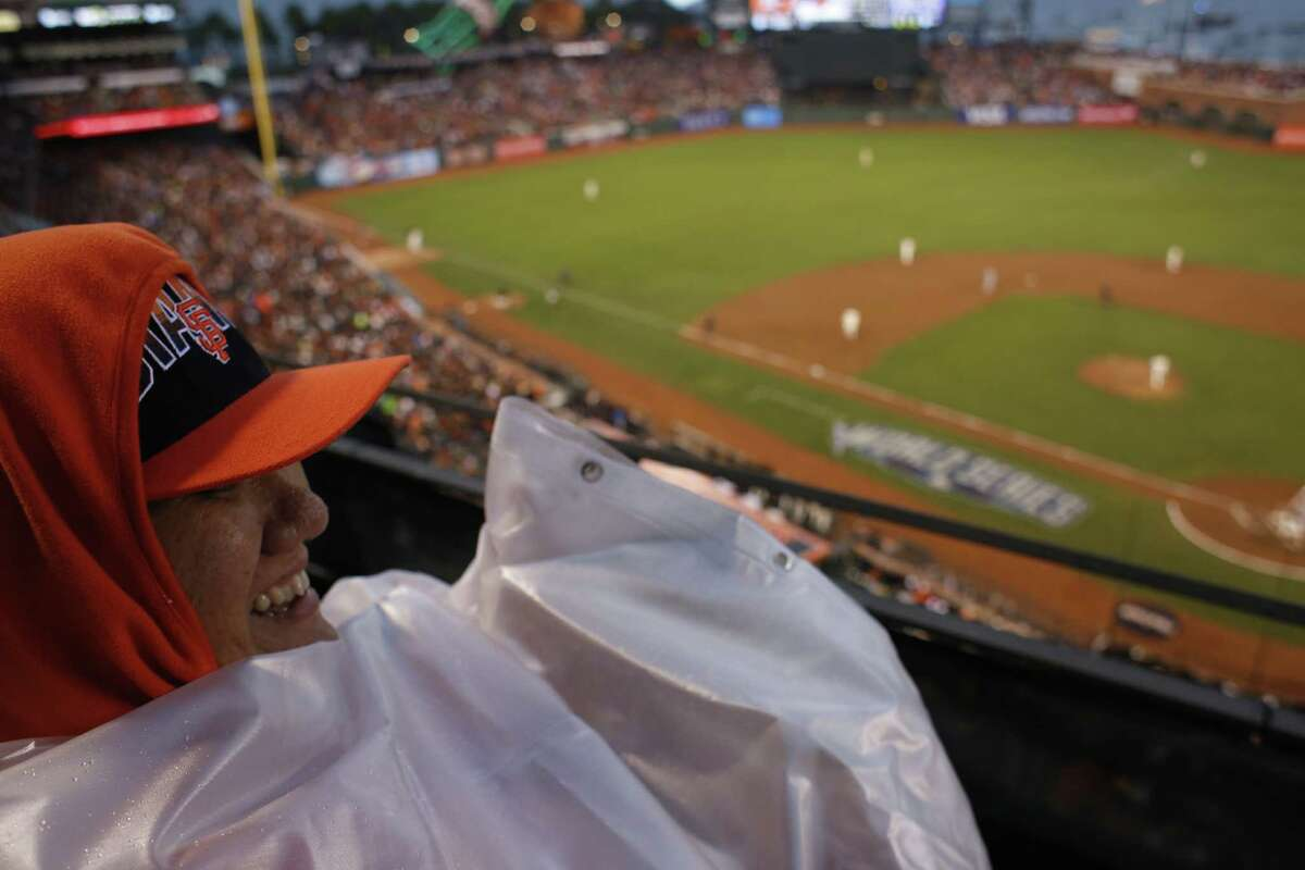 Giants fan Anne Chan, of San Francisco, came prepared for rain wearing a shower curtain for rain on the view level during game four of the World Series at AT&T park against the Kansas City Royals on Friday Oct. 25, 2014 in San Francisco, Calif.