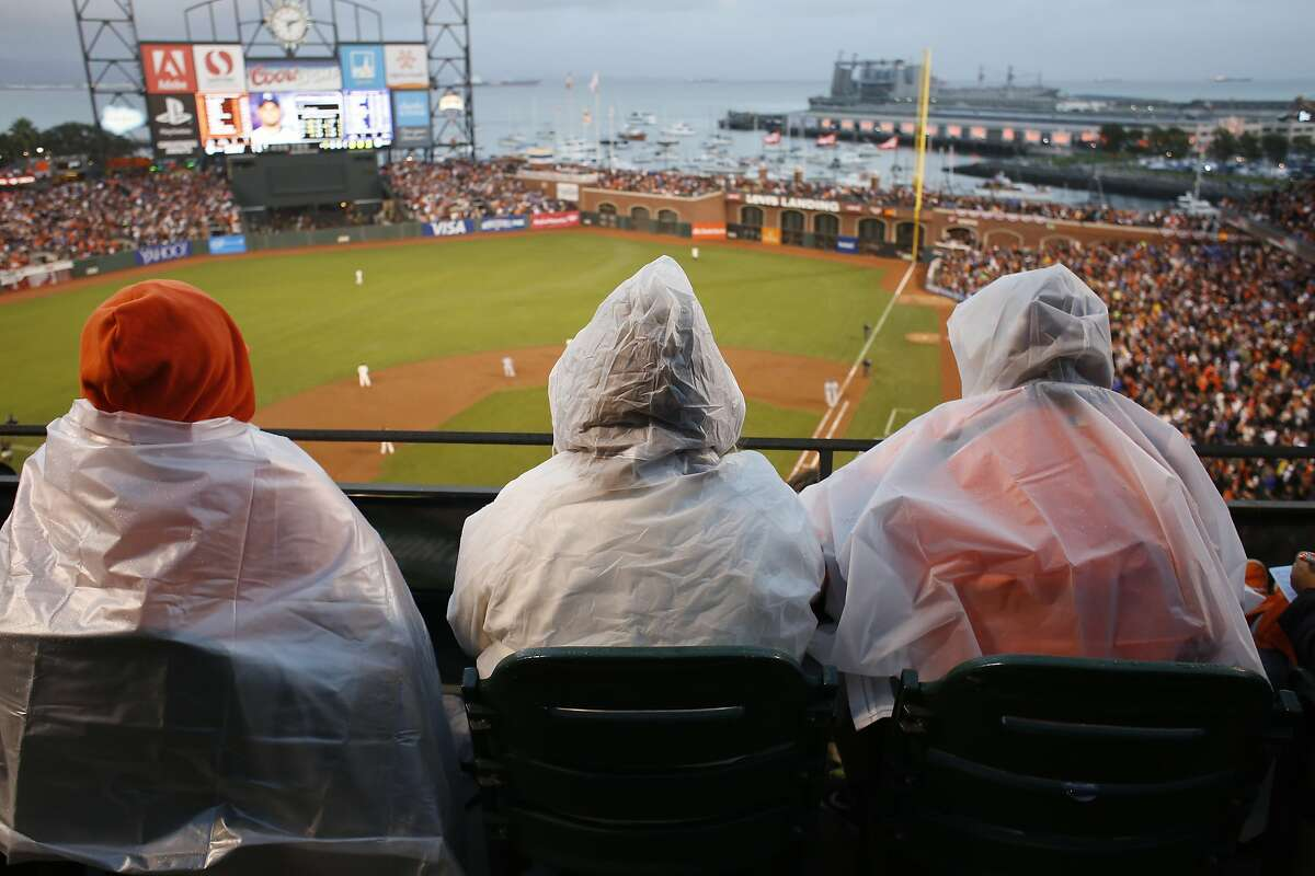 Giants fans Anne Chan, Claudia Fort and Monica Kraft, prepare for rain on the view level during game four of the World Series at AT&T park against the Kansas City Royals on Friday Oct. 25, 2014 in San Francisco, Calif.