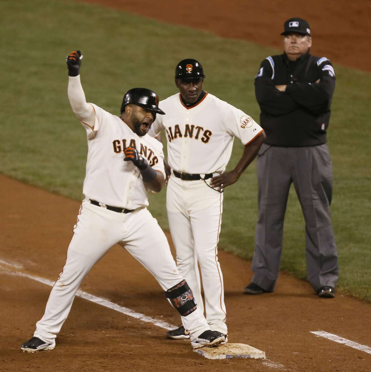 Giants Pablo Sandoval reacts at first base after hitting a sixth inning RBI during Game 4 of the World Series at AT&T Park on Saturday, Oct. 25, 2014 in San Francisco, Calif.