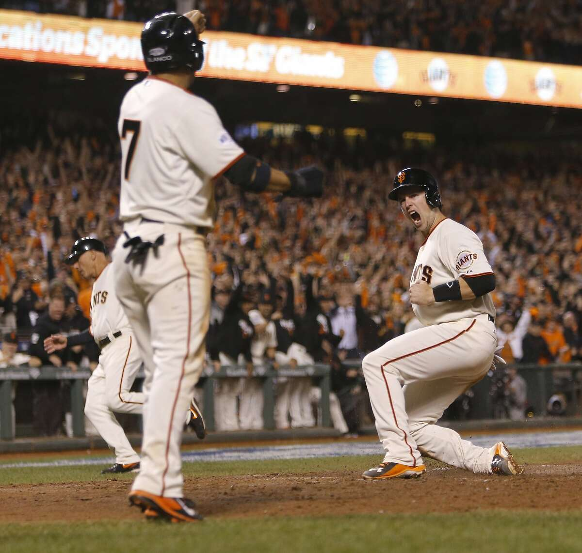 Giants Buster Posey scores reacts after scoring in the sixth on a two run single by Pablo Sandoval during Game 4 of the World Series at AT&T Park on Saturday, Oct. 25, 2014 in San Francisco, Calif.