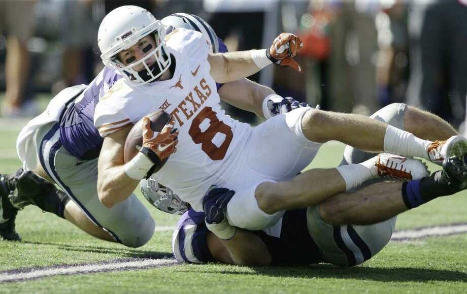 Kansas State linebackers Will Davis (back left) and Jonathan Truman tackle Texas wide receiver Jaxon Shipley during the second half. The Longhorns were held to 196 yards. Photo: Orlin Wagner / Associated Press / AP