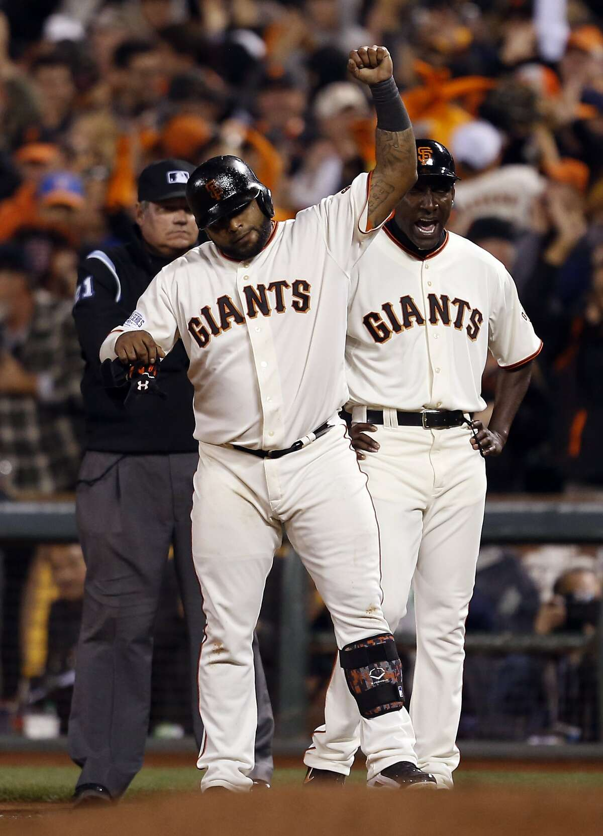 San Francisco Giants' Pablo Sandoval and 1st base coach Roberto Kelly celebrate Sandoval's 2 RBI single in 6th inning of 11-4 win over Kansas City Royals in Game 4 of the World Series at AT&T Park in San Francisco, Calif.. on Saturday, October 25, 2014.