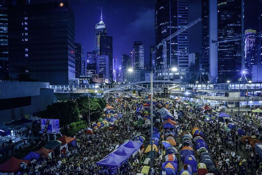 TOPSHOTS Pro-democracy protester gather at the main protest site in the Admiralty district of Hong Kong on October 24, 2014. Major intersections in the southern Chinese city have been paralysed by mass rallies demanding free elections for more than three weeks, in one of the biggest challenges to Beijing's authority since the Tiananmen pro-democracy protests of 1989.  AFP PHOTO / Philippe LopezPHILIPPE LOPEZ/AFP/Getty Images Photo: Philippe Lopez, AFP/Getty Images