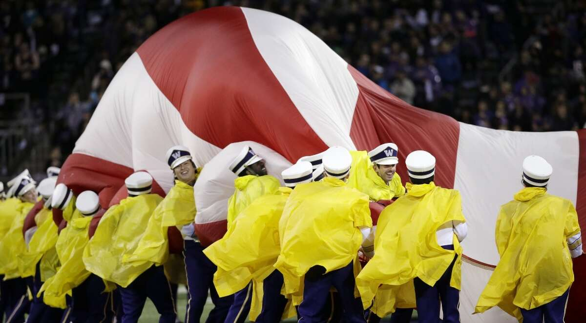 Members of the Washington band try to control a giant U.S. flag before Washington played against Arizona State in an NCAA college football game Saturday, Oct. 25, 2014, in Seattle. (AP Photo/Elaine Thompson)