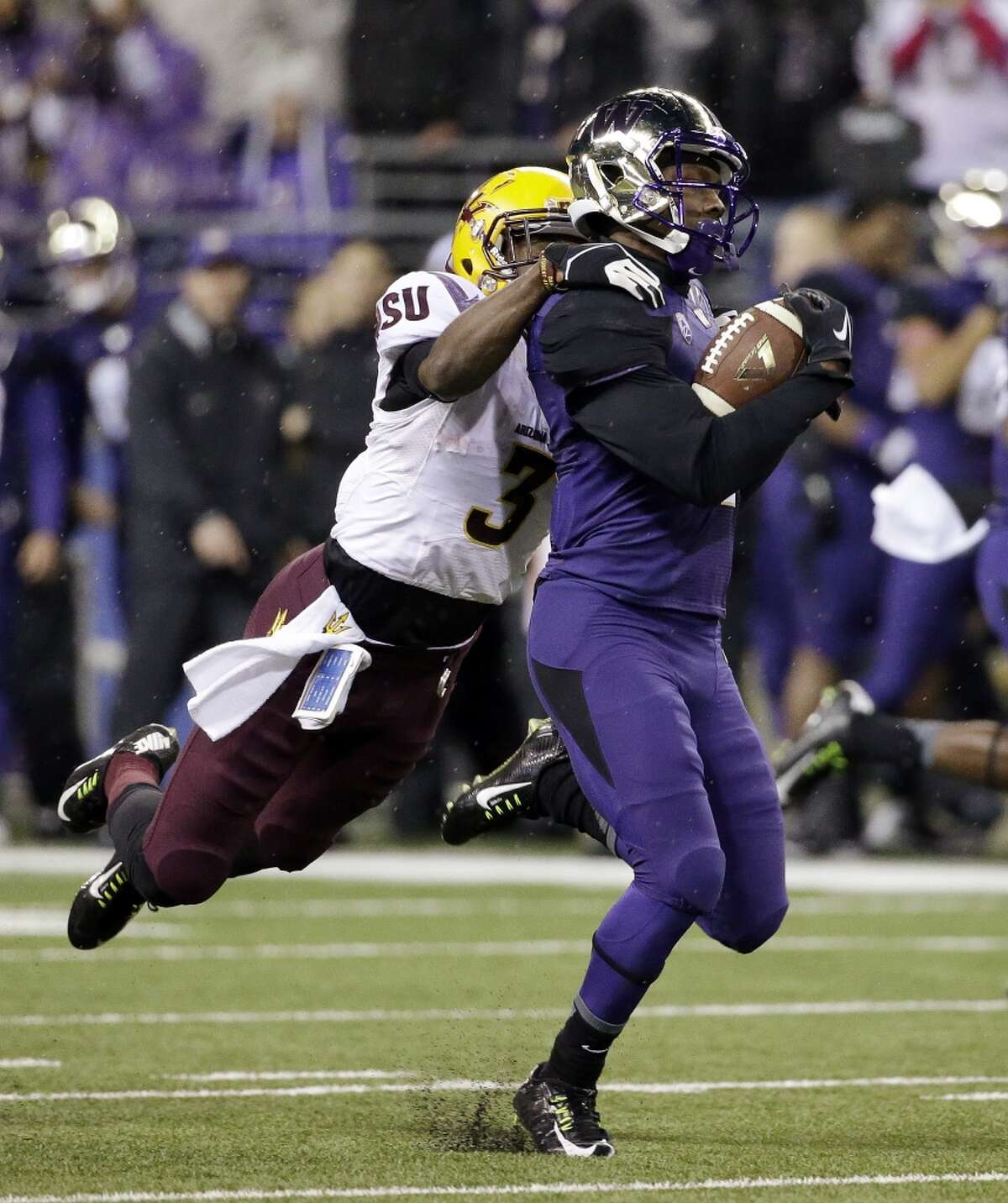Washington's John Ross, right, is brought down from behind by Arizona State's Damarious Randall on a kickoff return late in the first half of an NCAA college football game Saturday, Oct. 25, 2014, in Seattle. Ross' long run was called back on a penalty. (AP Photo/Elaine Thompson)