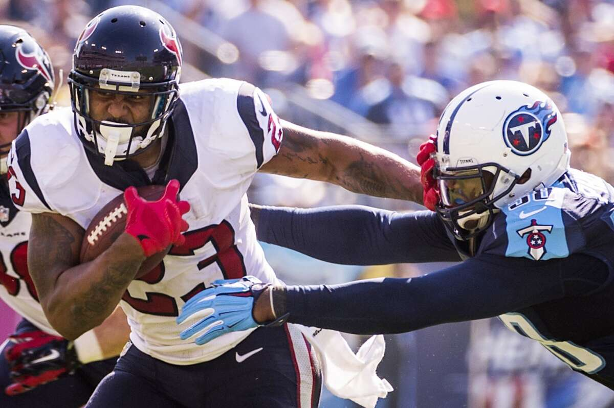 Houston Texans running back Arian Foster (23) pushes away from Tennessee Titans outside linebacker Shaun Phillips (58) during the first half an NFL football game at LP Field on Sunday, Oct. 26, 2014, in Nashville. ( Smiley N. Pool / Houston Chronicle )