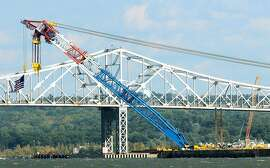 PIERMONT, NY - OCTOBER 6:  The Left Coast Lifter, one of the world's largest floating cranes, is put in position in front of the Tappan Zee Bridge on the Hudson River on October 6, 2014 seen from Piermont, New York. The super crane was brought over from California to aid in the replacement of Tappan Zee Bridge and construction of the New New York Bridge that connects Rockland and Westchester counties. The crane has a boom length of 328 feet, can lift 1,900 tons and sits on a 384-foot barge.  (Photo by Jim Alcorn/Getty Images)