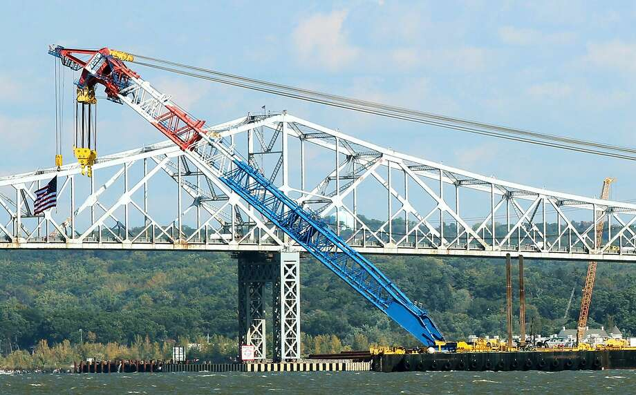 The Left Coast Lifter, one of the world's largest floating cranes, is put in position in front of the Tappan Zee Bridge on the Hudson River on October 6, 2014 seen from Piermont, New York. The super crane was brought over from California to aid in the replacement of Tappan Zee Bridge and construction of the New New York Bridge that connects Rockland and Westchester counties. The crane has a boom length of 328 feet, can lift 1,900 tons and sits on a 384-foot barge.  Photo: Jim Alcorn, Getty Images