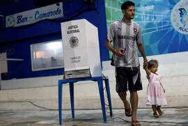 A man with a child leaves after voting at the Rocinha favela in Rio de Janeiro in the close runoff election.
