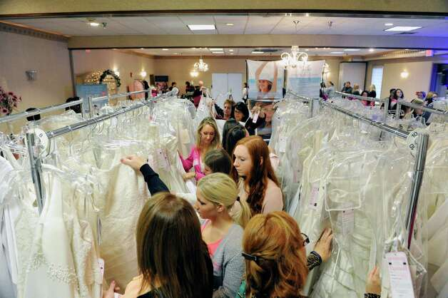 Women search the racks of donated bridal dresses during the Brides Against Breast Cancer event at the Best Western Albany Airport Inn on Sunday, Oct. 26, 2014, in Albany, N.Y. The event sells donated wedding dresses and funds raised go towards programs for cancer patients and their families.  (Paul Buckowski / Times Union) Photo: Paul Buckowski / 00029195A