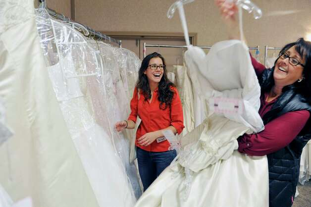 Allee Keener, left, from Troy and her mother, Debbie Keener, also from Troy, search fora  wedding dress for Allee during the Brides Against Breast Cancer event at the Best Western Albany Airport Inn on Sunday, Oct. 26, 2014, in Albany, N.Y.  Allee is getting married this coming summer.  The Brides Against Breast Cancer event sells donated wedding dresses and funds raised go towards programs for cancer patients and their families.  (Paul Buckowski / Times Union) Photo: Paul Buckowski / 00029195A
