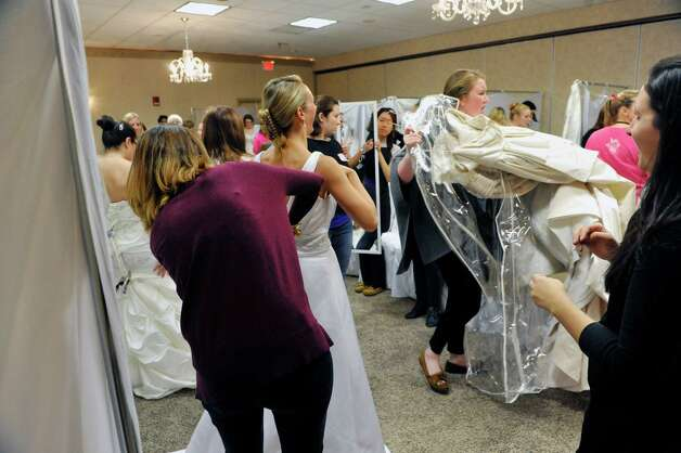 Women try on bridal dresses during the Brides Against Breast Cancer event at the Best Western Albany Airport Inn on Sunday, Oct. 26, 2014, in Albany, N.Y. The event sells donated wedding dresses and funds raised go towards programs for cancer patients and their families.  (Paul Buckowski / Times Union) Photo: Paul Buckowski / 00029195A