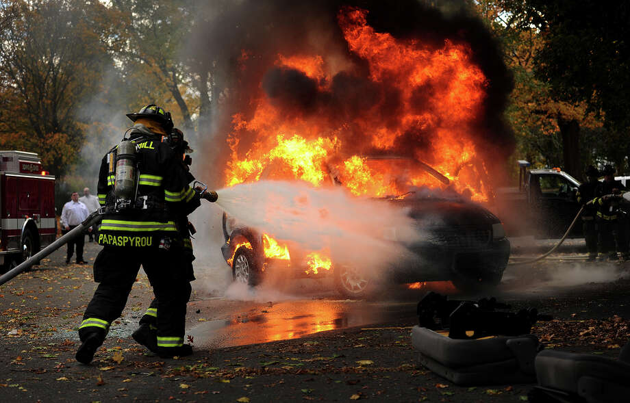 Volunteer firefighters extinguish a car fire, one of several firefighting demonstrations during an open house at Long Hill Fire Department's Station 1 at 6315 Main Street in Trumbull, Conn. on Sunday, October 26, 2014. Photo: Brian A. Pounds / Connecticut Post