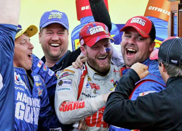 Dale Earnhardt Jr., center, celebrates with his pit crew after winning the NASCAR Sprint Cup Series auto race at Martinsville Speedway in Martinsville, Va., Sunday, Oct. 26, 2014. (AP Photo/Steve Helber) ORG XMIT: VASH124 Photo: Steve Helber / AP