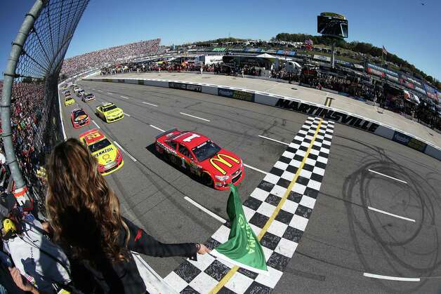 In this photo provided by NASCAR and taken with a fisheye lens, Jamie McMurray (1) and Joey Logano, (22) lead the field to the green flag for the running of the NASCAR Sprint Cup Series auto race at Martinsville Speedway, Sunday, Oct. 26, 2014, in Martinsville, Va. (AP Photo/NASCAR, Sarah Glenn) ORG XMIT: VASH115 Photo: Sarah Glenn / NASCAR