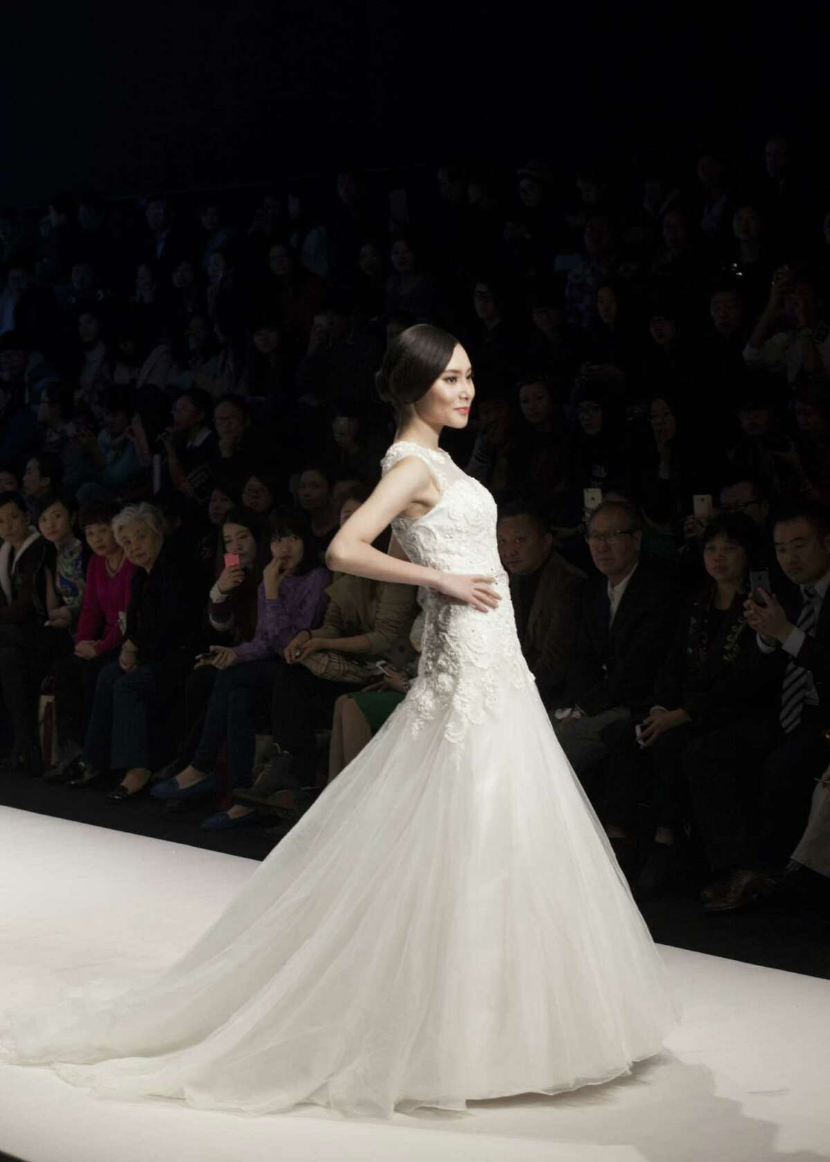 A model showcases designs on the runway at Famory Bridal Collection show during the Mercedes-Benz China Fashion Week Spring/Summer 2015 at Beijing Hotel on October 26, 2014 in Beijing, China. (Photo by Katharina Hesse/Anadolu Agency/Getty Images)