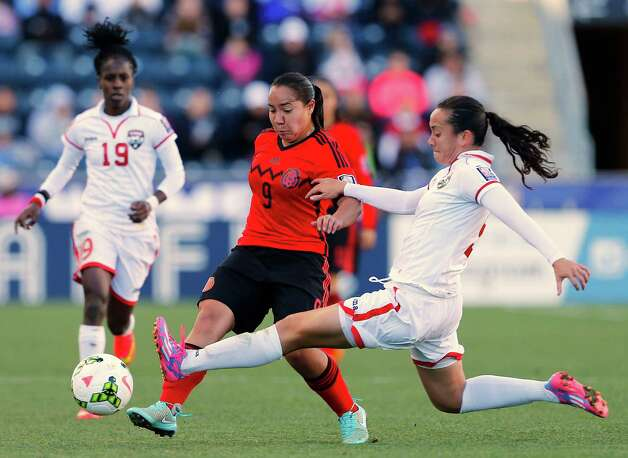 Mexico forward Veronica Charlyn Corral (9) attempts to move the ball past Trinidad and Tobago defender Arin King (5) in overtime during a CONCACAF consolation soccer match in Chester, Pa., Sunday, Oct. 26, 2014. Mexico defeated Trinidad and Tobago 4-2 in overtime. (AP Photo/Rich Schultz) ORG XMIT: PARS107 Photo: RICH SCHULTZ / FR27227 AP